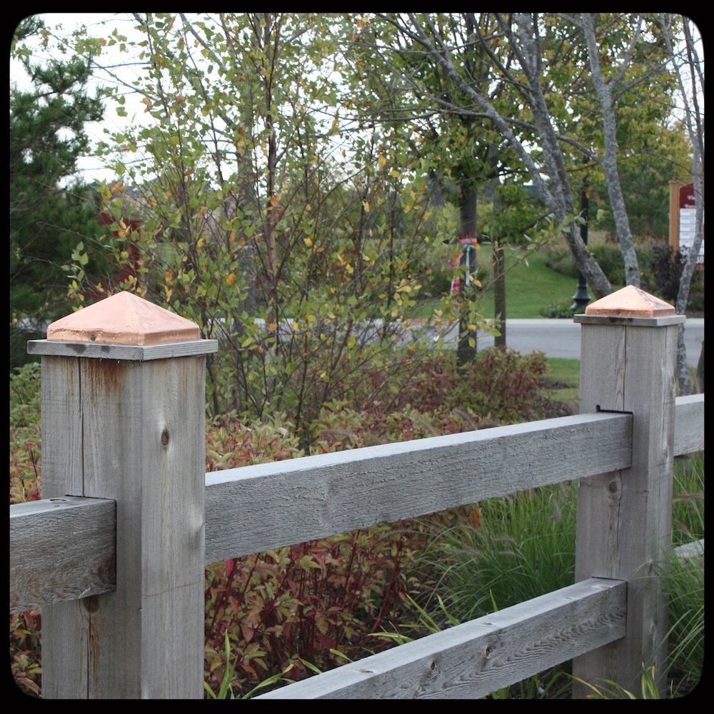 copper pyramid fence post caps on wooden fence